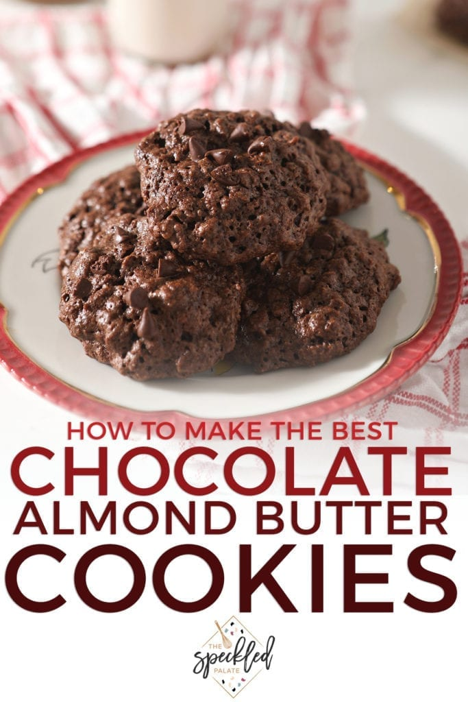 A stack of Chocolate Almond Butter Cookies with Chocolate Chips sit on a red-rimmed plate sitting on a red plaid towel with the text 'how to make the best chocolate almond butter cookies'