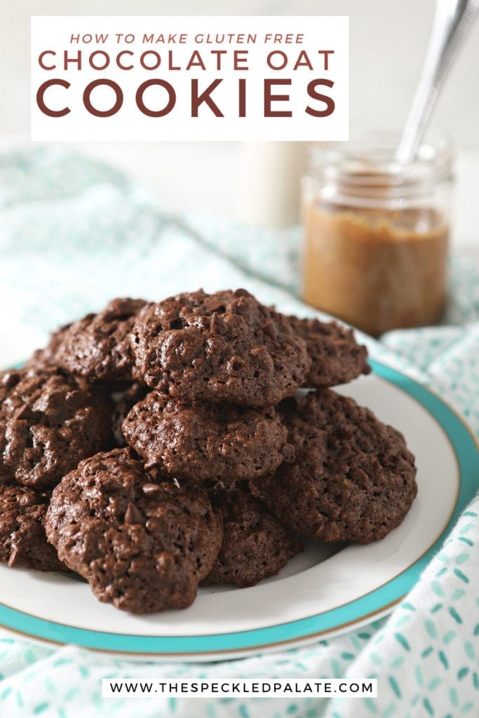 A turquoise-rimmed plate holds a stack of chocolate almond oat cookies sitting on a patterned aqua and white towel with a jar of almond butter and a glass of almond milk behind it with the text 'how to make gluten free chocolate oat cookies'