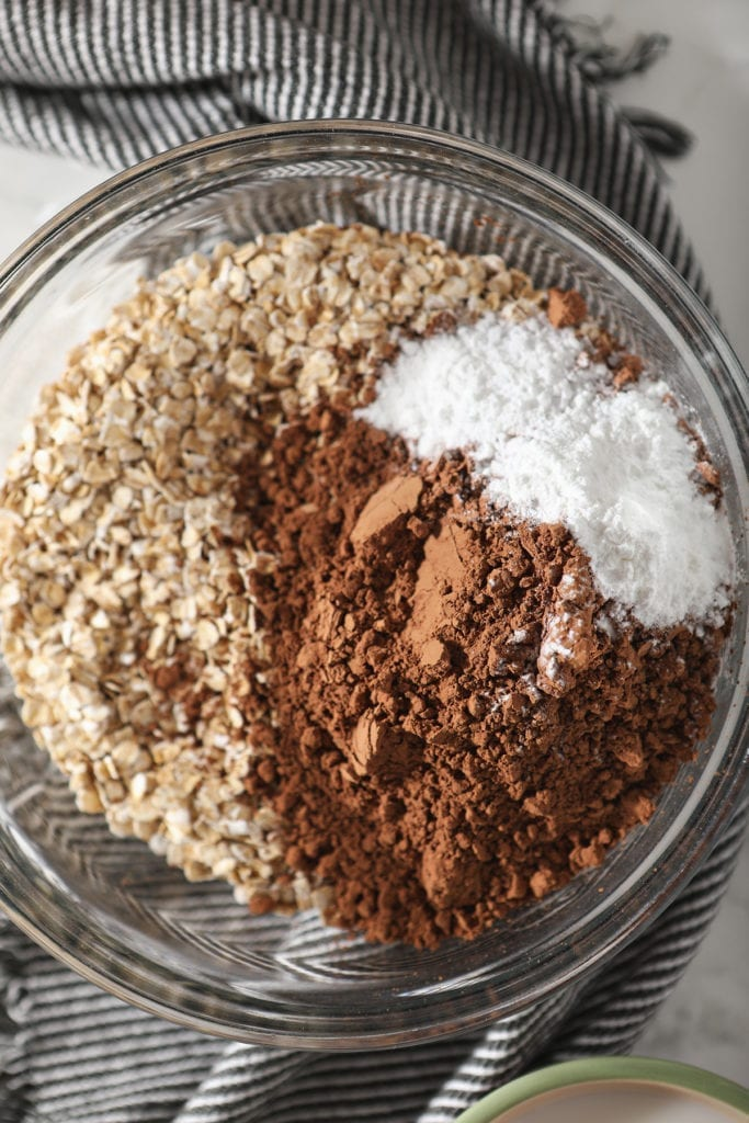 Rolled oats, cocoa powder, salt and baking powder in a bowl on top of a gray and white striped towel