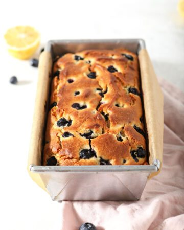 A loaf of Lemon Blueberry Bread in a loaf pan on marble