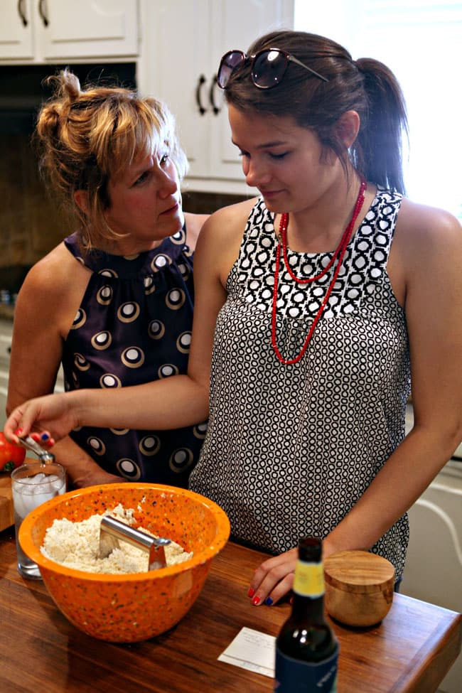 A blond woman and a brunette woman stand together in front of an orange bowl holding pie crust ingredients as they make a pie