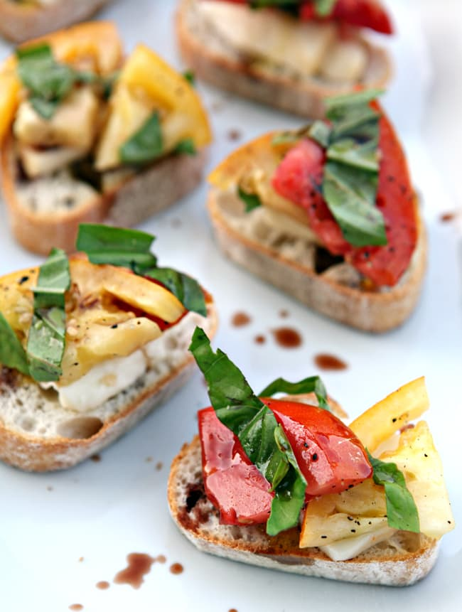 Before the summer ends, celebrate the season with this super quick and easy Heirloom Tomato Bruschetta. Slice four ripe heirloom tomatoes, and place them on top of French bread slices and fresh mozzarella slices to make this beautiful appetizer.