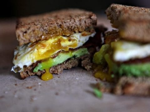 The side view of a halved breakfast sandwich with the yolk of an egg running out of it