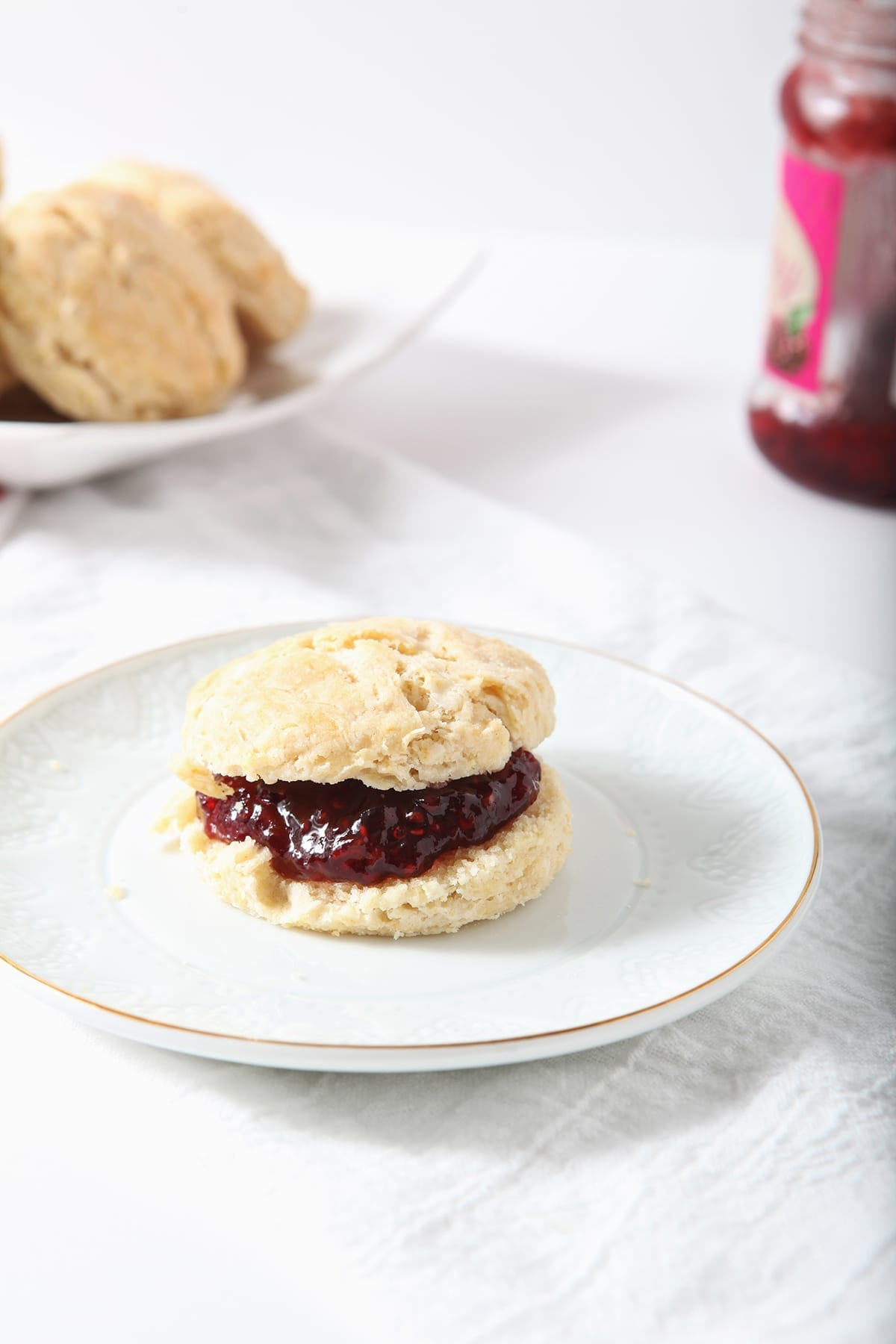 A biscuit with raspberry jam on a white plate with other biscuits and jam in the background
