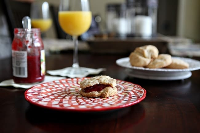 A side view of a biscuit with jam on a red plate on a dark wooden tabletop with mimosas, a jar of jam and other biscuits
