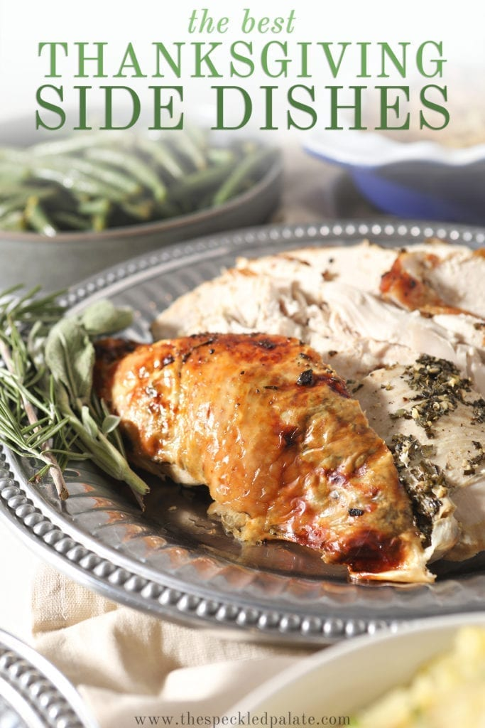 Close up of Turkey Brest on a silver platter surrounded by side dishes with the text 'the best thanksgiving side dishes'