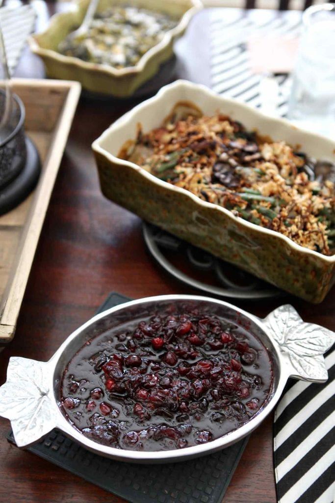 A serving of cranberry sauce sits in a silver bowl next to green bean casserole and other dishes on the holiday table