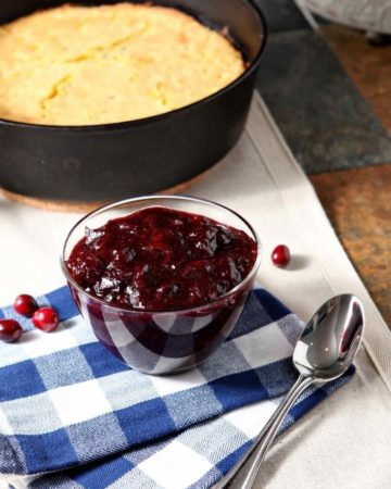 A small glass bowl holds Spiced Cranberry Sauce on top of a buffalo check towel next to cornbread