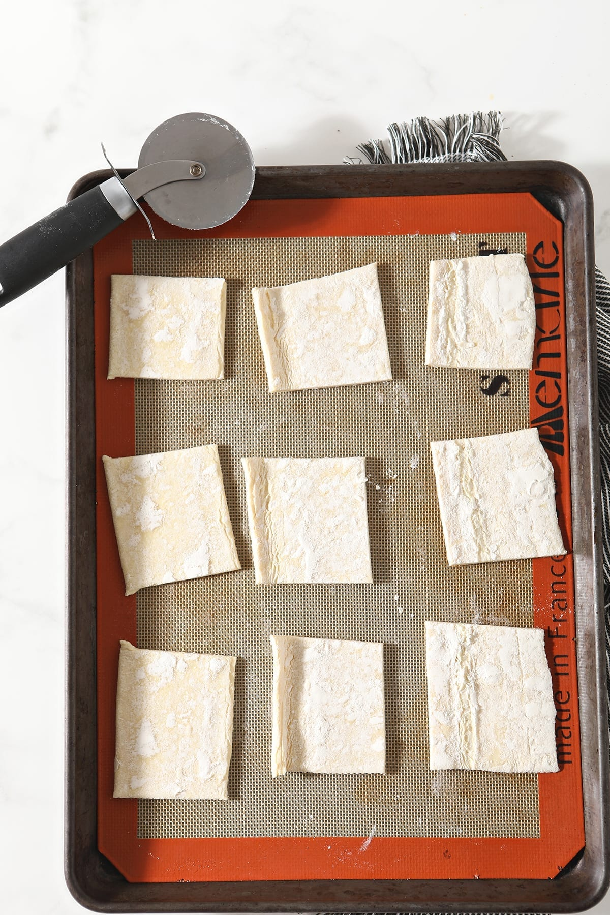 Squares of puff pastry on a Silpat-lined baking sheet with a pizza cutter