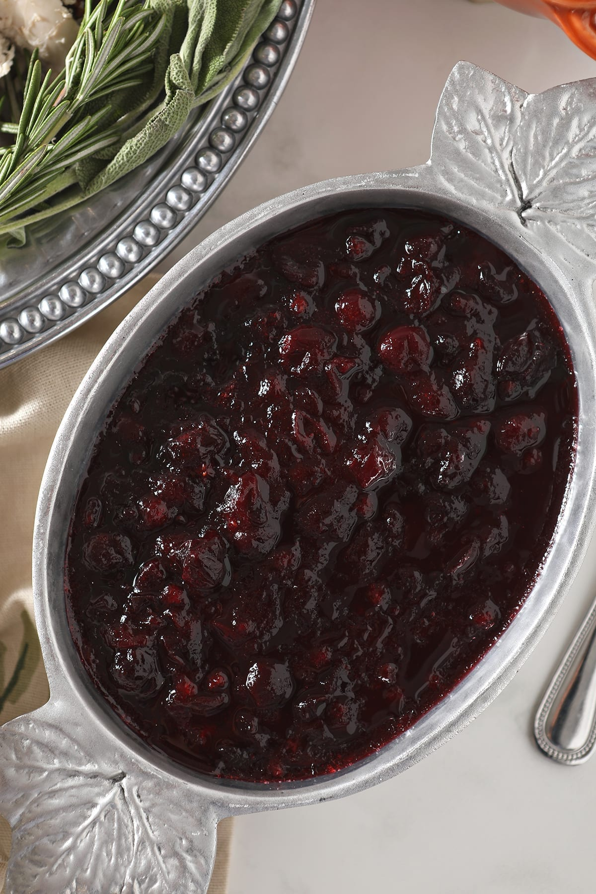 Close up of chilled spiced cranberry sauce in a silver serving bowl with maple leafs on the corners