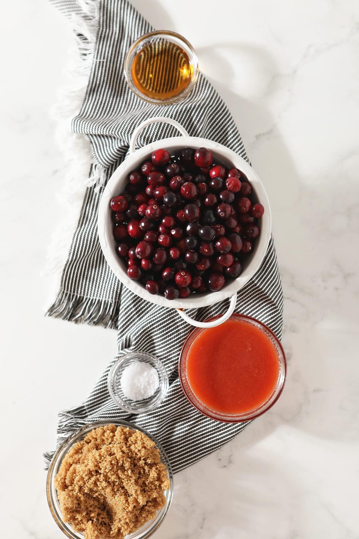 Fresh cranberries, orange juice, brown sugar, salt, and rum on a gray striped towel