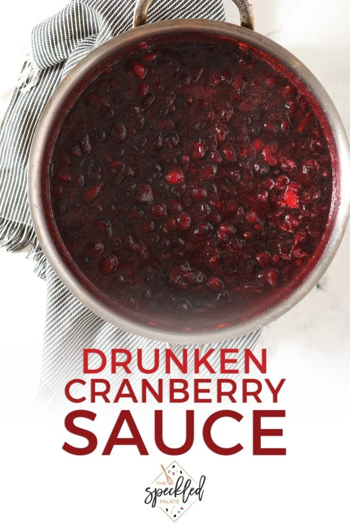 Hot cranberry sauce in a skillet on top of a gray striped towel with the text 'drunken cranberry sauce'