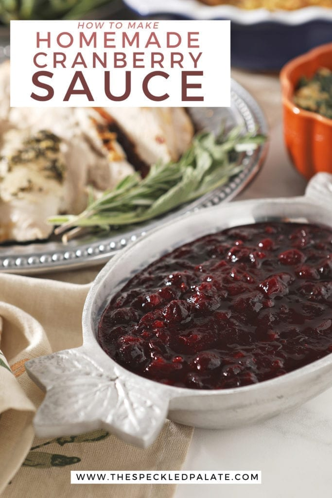 Cranberry sauce in a silver bowl with leafs on the ends next to a silver platter of turkey with the text 'how to make homemade cranberry sauce'