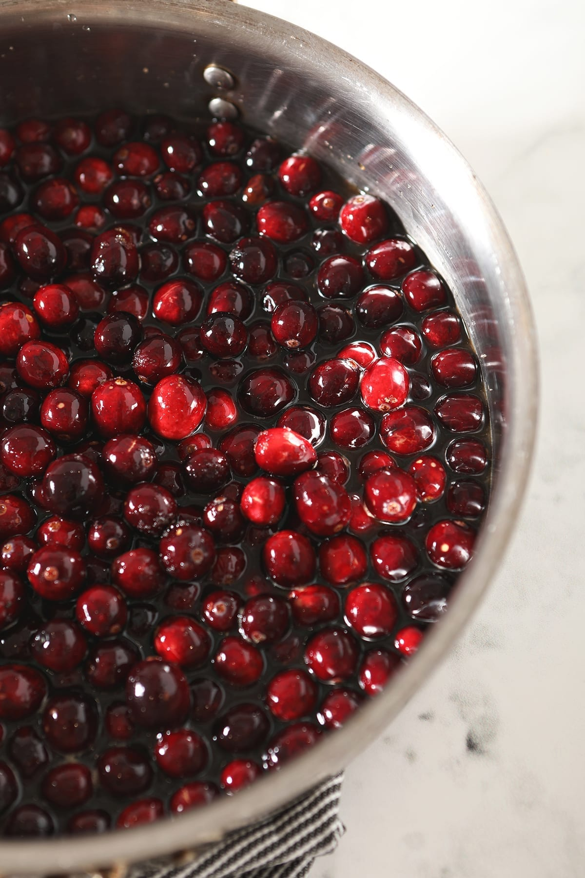 Cranberries cook down in a skillet