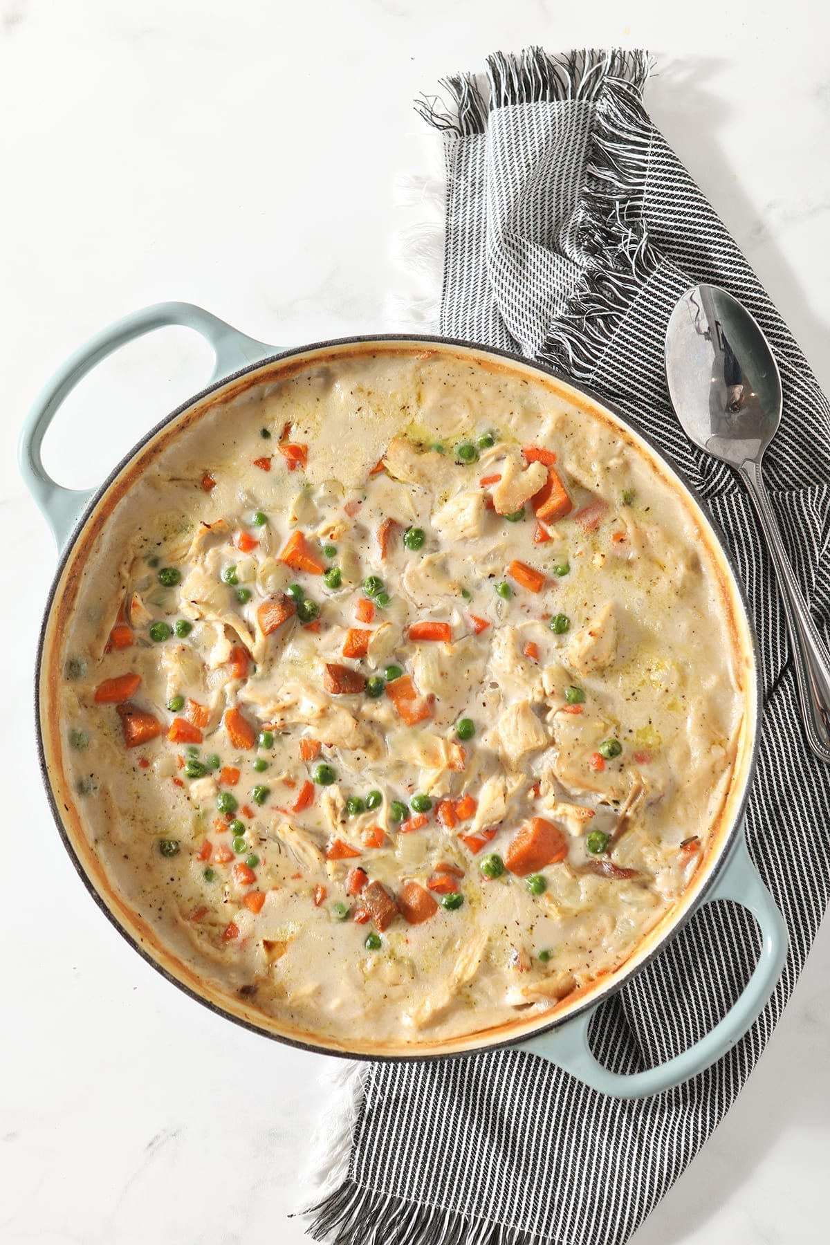 A dish holds turkey pot pie after baking in the oven on top of a striped gray towel with a large serving spoon