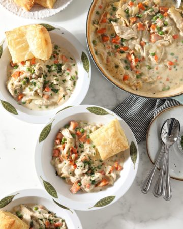 Three servings of Turkey Pot Pie in decorative dishes sit next to the casserole dish, a plate holding baked puff pastry squares and a plate holding spoons