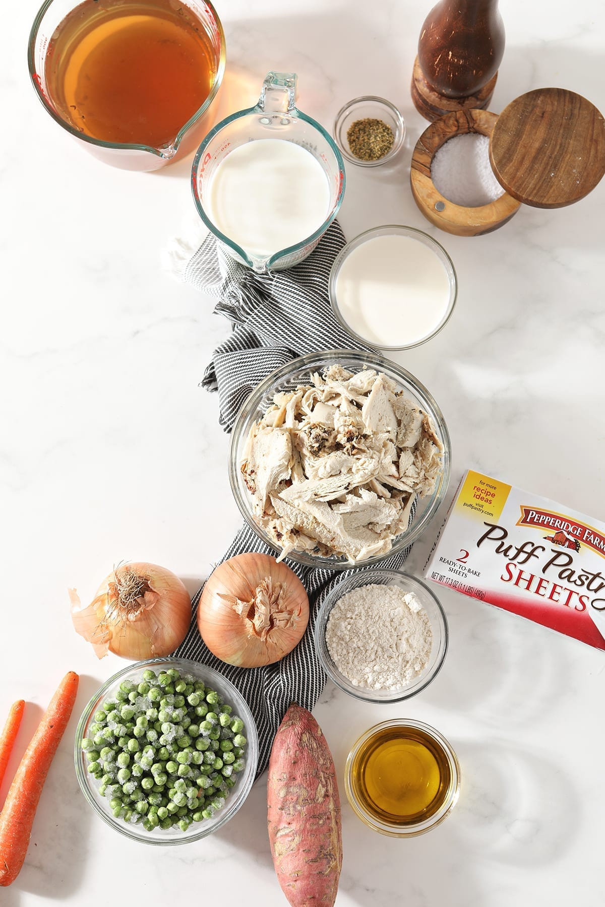 Shredded leftover turkey breast, vegetables, stock and milk, among other ingredients, sit on a gray striped towel on a marble countertop in bowls