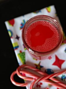 A jar of infused Candy Cane Vodka sits on a holiday cloth with candy canes surrounding it
