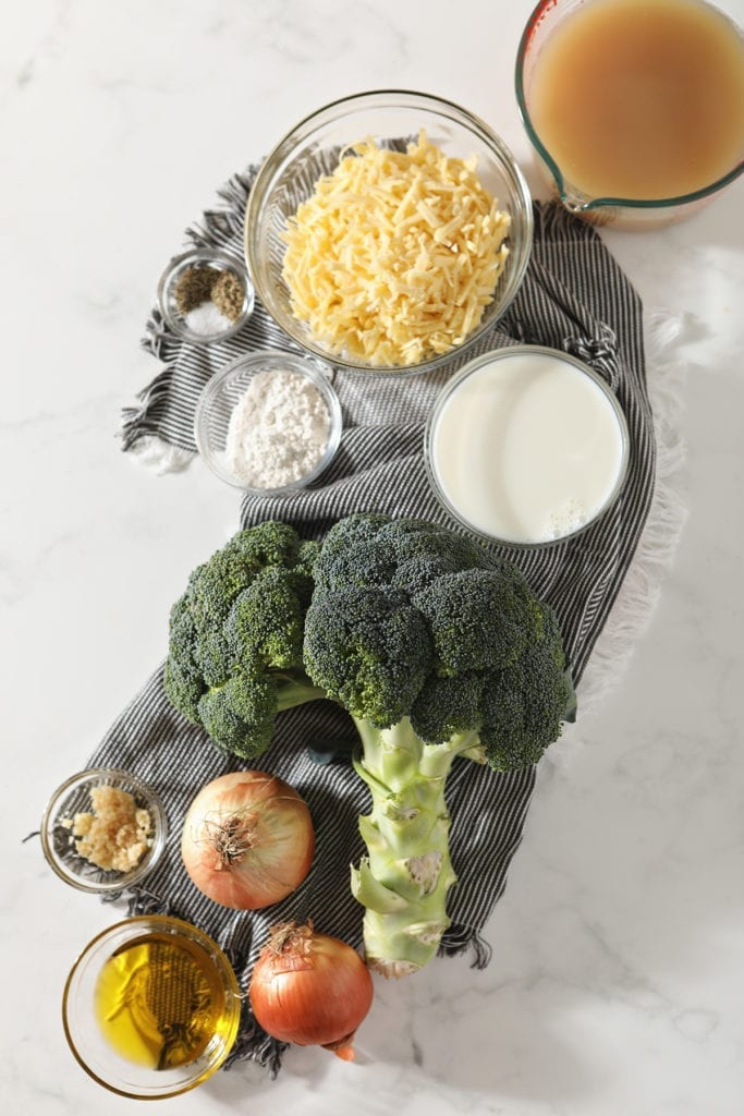 Ingredients for broccoli cheddar soup on a marble countertop in bowls