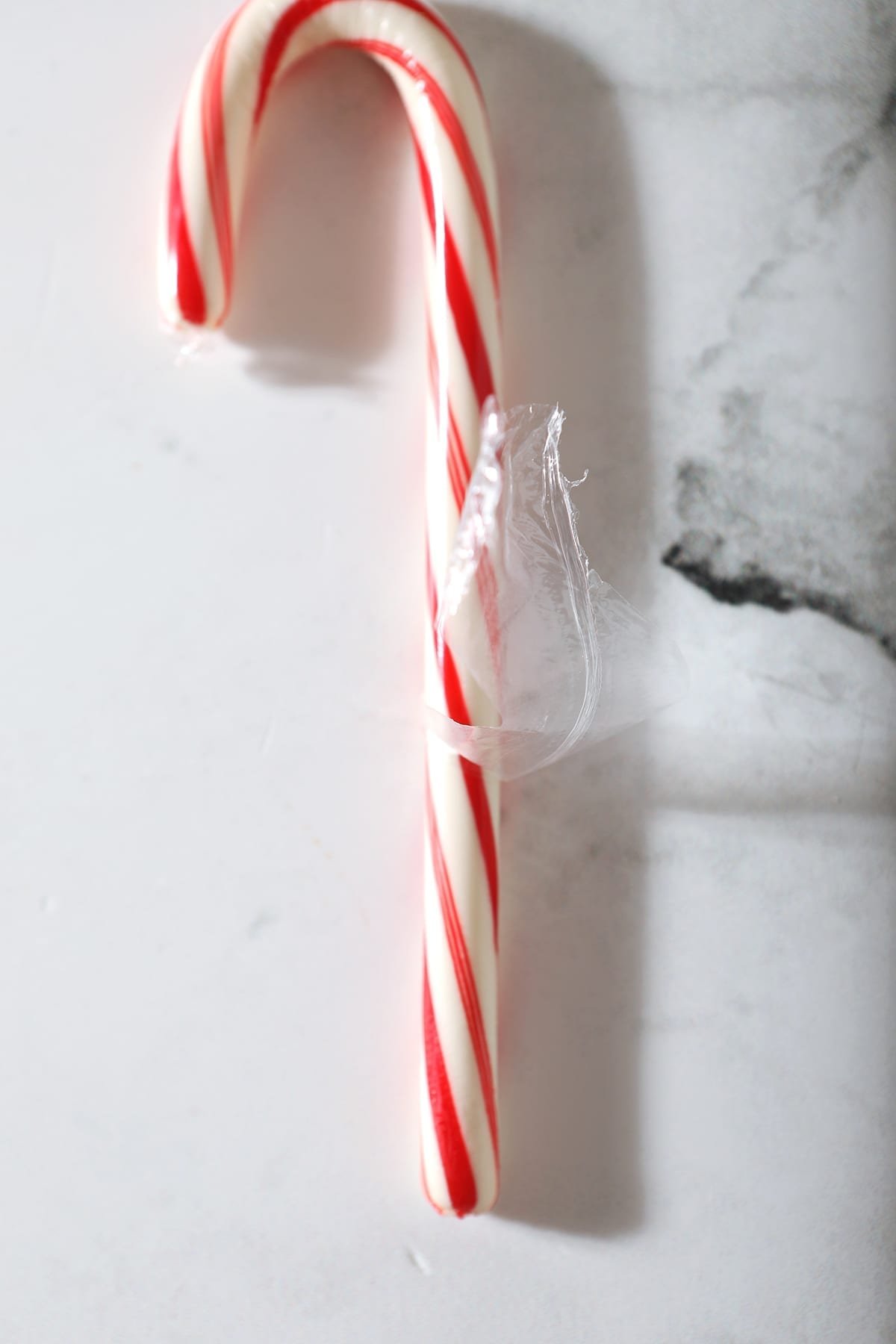 Close up of a half-peeled candy cane on marble