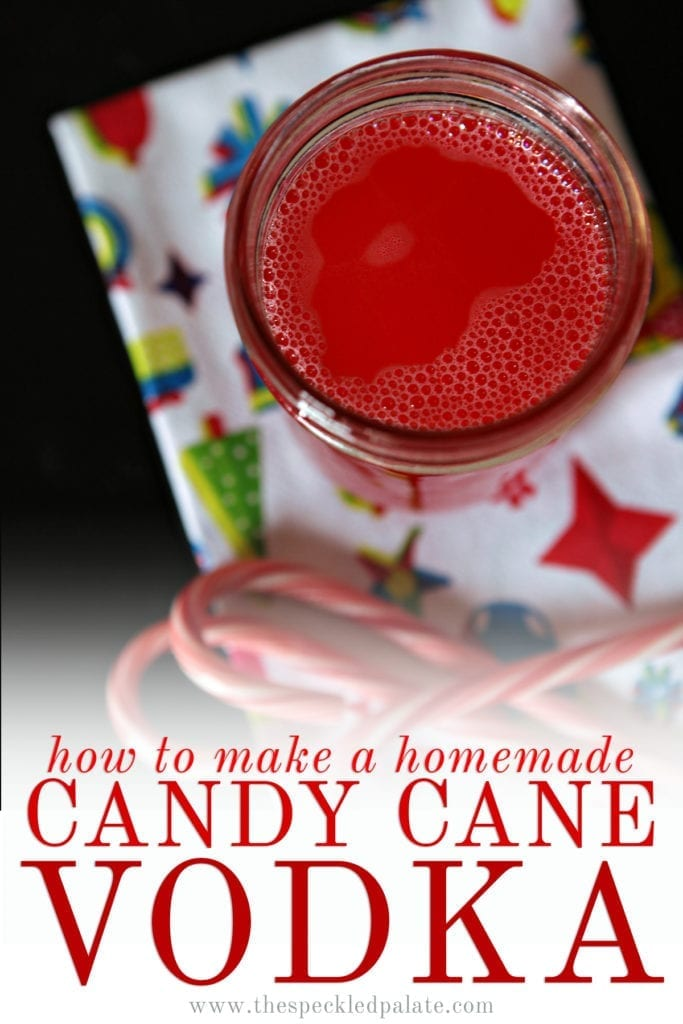 Close up of a mason jar of peppermint vodka next to candy canes on a Christmas-patterned white towel with the text 'how to make a homemade candy cane vodka'