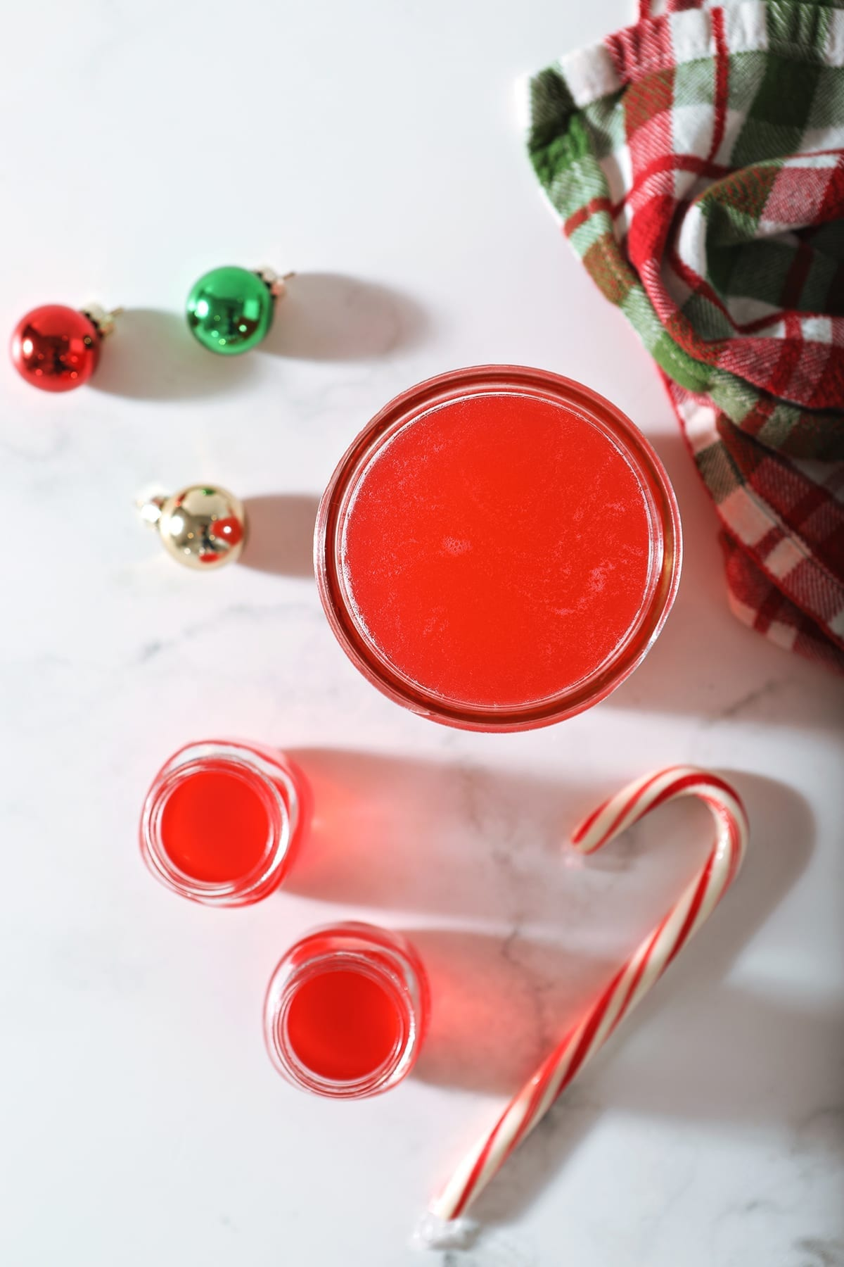 Two shot glasses of peppermint vodka sit next to a mason jar full of the candy cane-infused vodka with glass ornaments, a Christmas-colored plaid towel and a candy cane on marble
