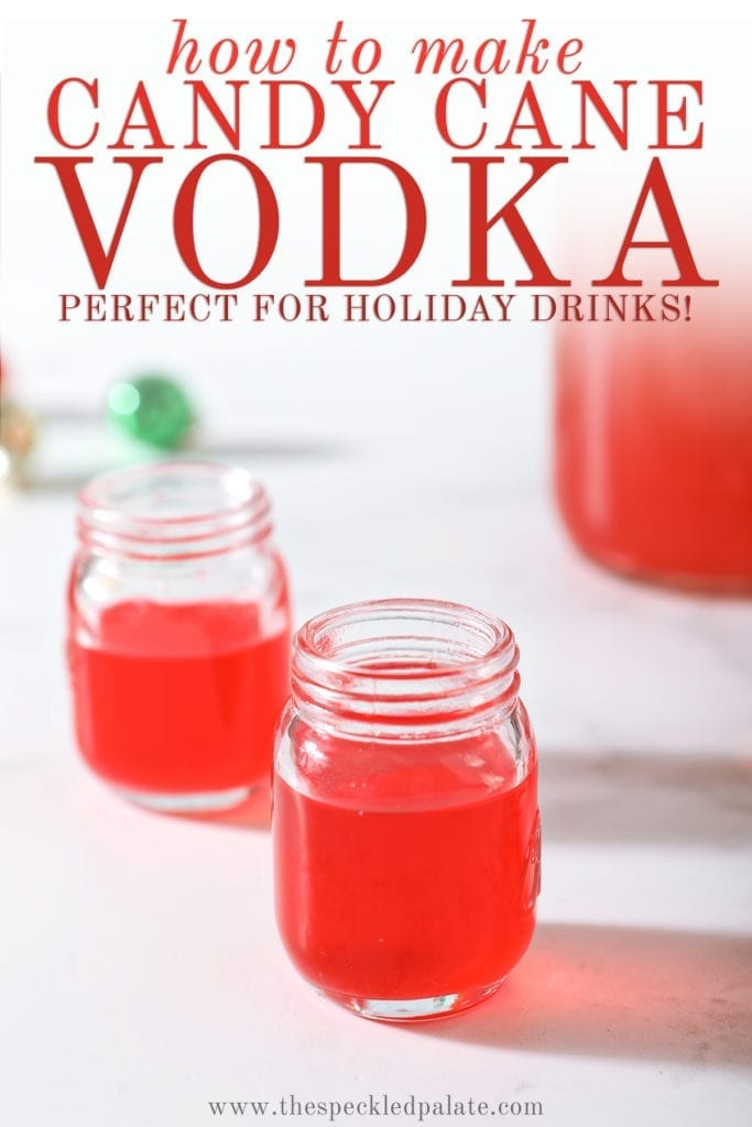 Two shot glasses of peppermint vodka on a marble surface next to a mason jar full of the candy cane-infused vodka with the text 'how to make candy cane vodka. perfect for holiday drinks!'