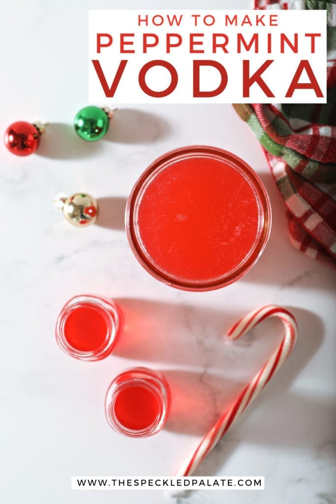 Two shot glasses of peppermint vodka sit next to a mason jar full of the candy cane-infused vodka with glass ornaments, a Christmas-colored plaid towel and a candy cane on marble with the text 'how to make peppermint vodka'