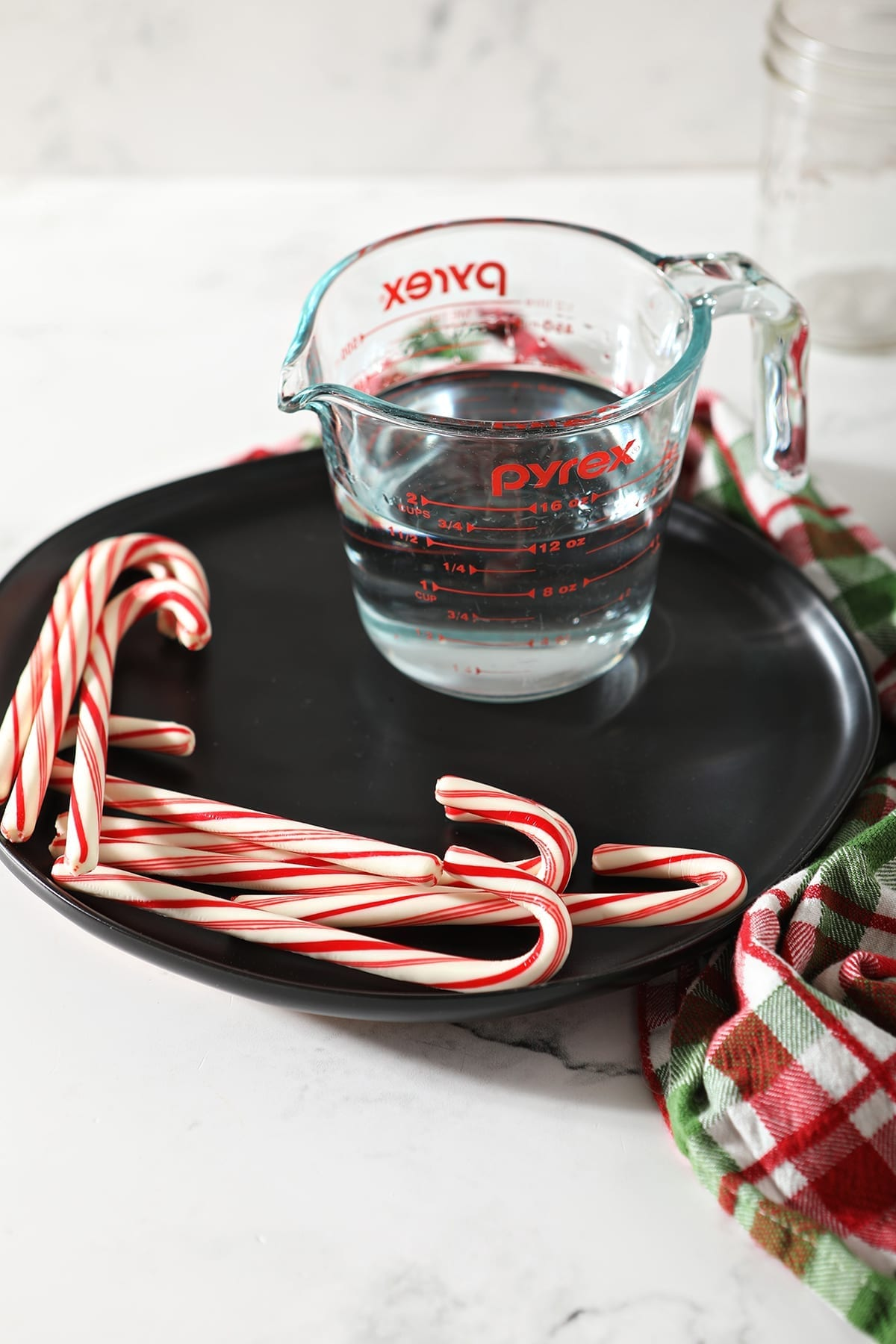 a measuring cup with peppermint vodka on a black plate with peppermint sticks