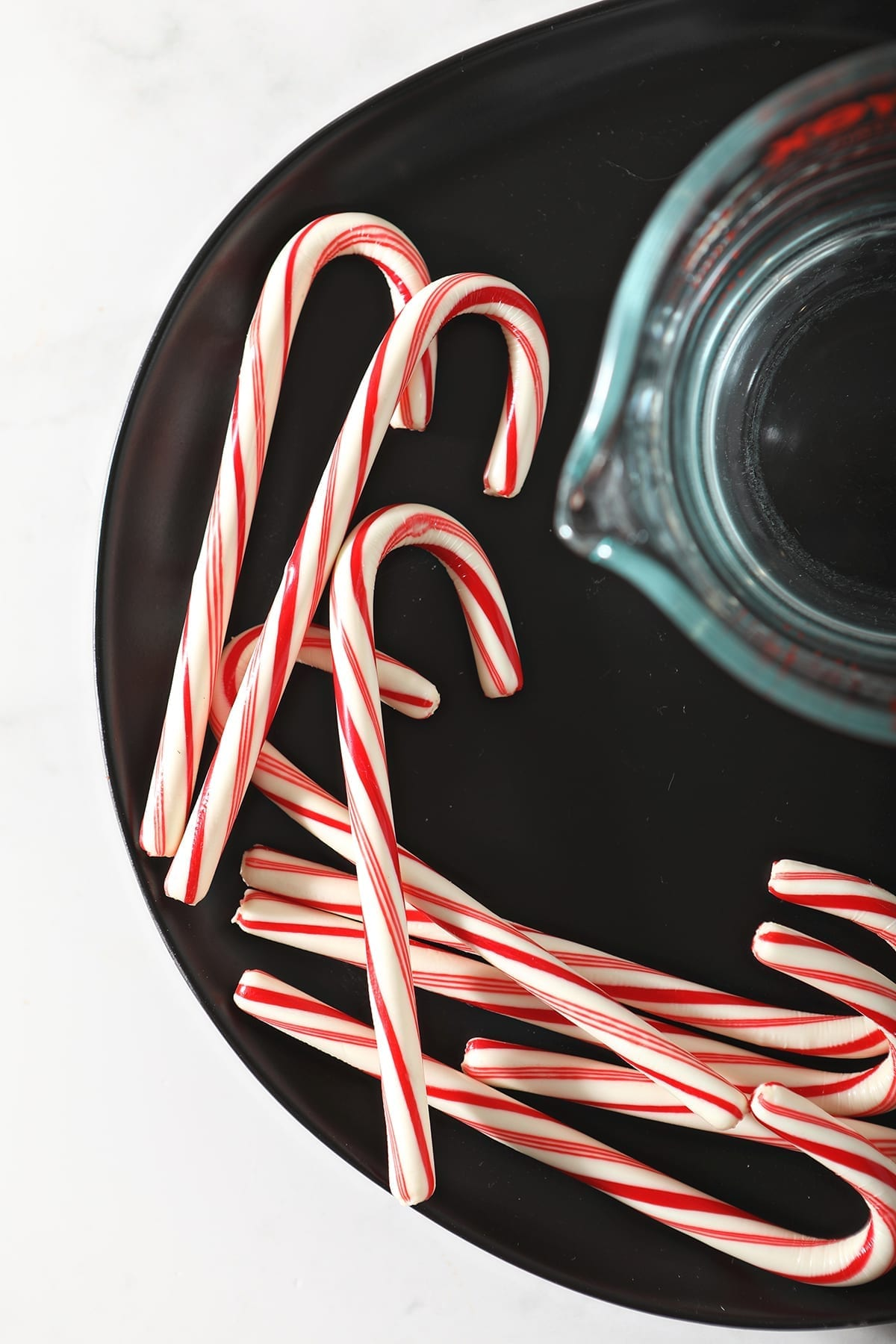 Close up of candy canes next to a measuring cup of vodka on a black plate
