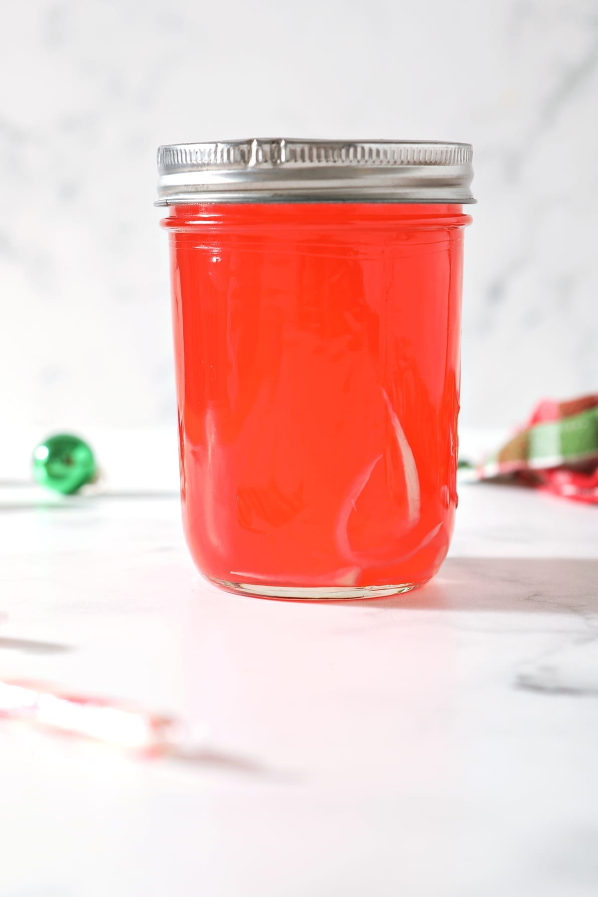 A bright red liquid is left in a mason jar after candy canes dissolve into vodka