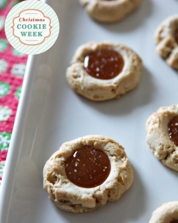Close up of thumbprint cookies on a white tray with caramel