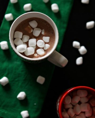 Overhead of two mugs holding dairy free hot chocolate with mini marshmallows in the mugs sitting on a green cloth