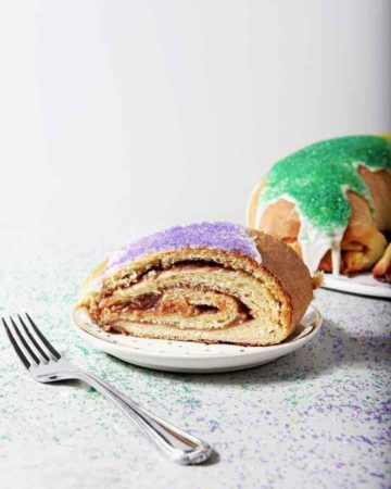 A slice of Cream Cheese and Raspberry King Cake sits in front of the whole King Cake