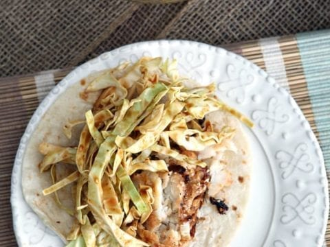 Overhead image of Soy Seared Cod Tacos with Spicy Slaw, placed on a white plate before eating