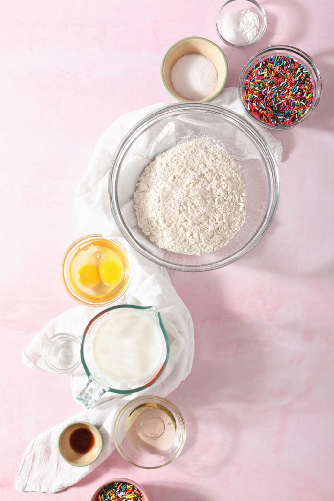 Ingredients for birthday cake pancakes in bowls on a pink countertop