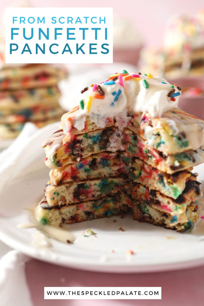 A cut-into stack of rainbow sprinkle pancakes on a white plate with the text from scratch funfetti pancakes