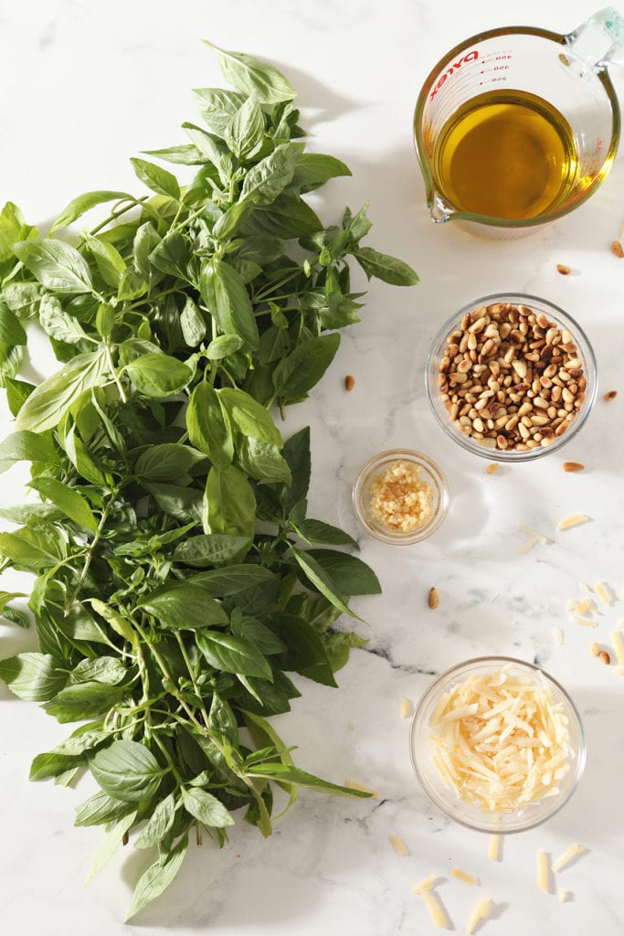 Fresh basil leaves next to oil, pine nuts, garlic and parmesan in bowls