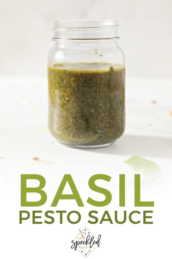 A jar of homemade pesto on marble with the text basil pesto sauce