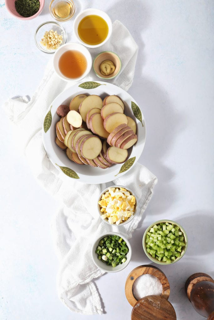 Sliced red potatoes with other homemade potato salad ingredients in bowls