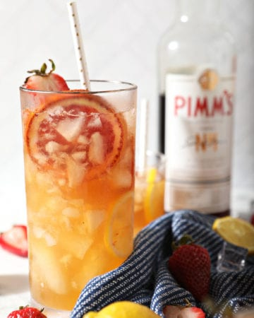 A glass of Pimms Punch garnished with strawberry and blood orange in front of a Pimm's No. 1 bottle