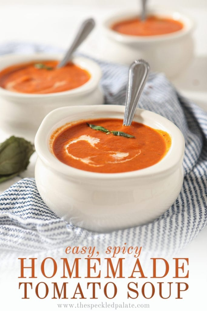 Close up of a white bowl holding spicy tomato soup with a swirl of cream and basil leaves on top with the text 'easy, spicy homemade tomato soup'