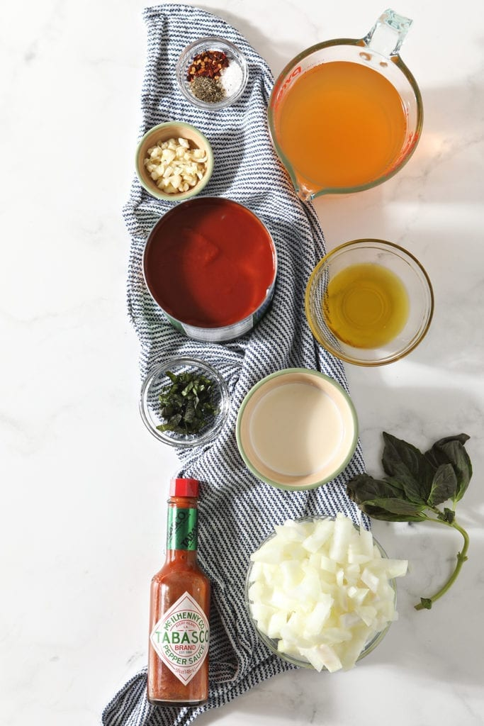 Ingredients for soup sit on a blue striped towel on a marble counter