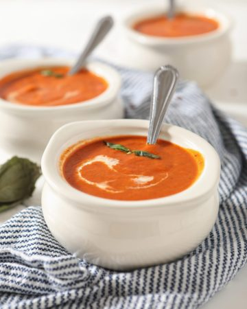 Close up of a white bowl holding spicy tomato soup with a swirl of cream and basil leaves on top