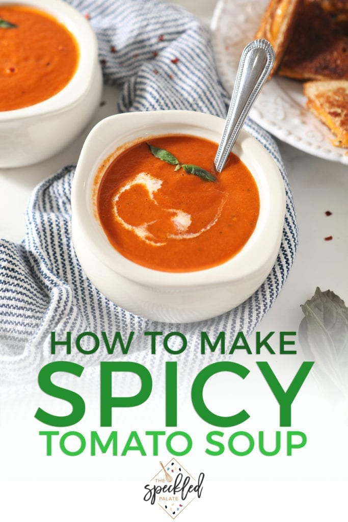 A bowl of tomato soup with a swirl of cream and basil leaves sits on a blue striped towel with the text 'how to make spicy tomato soup'