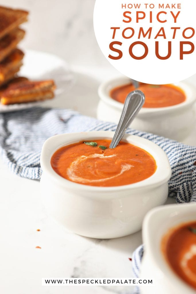 Three pottery bowls of tomato soup with spoons in them on a blue striped towel with the text 'how to make spicy tomato soup'