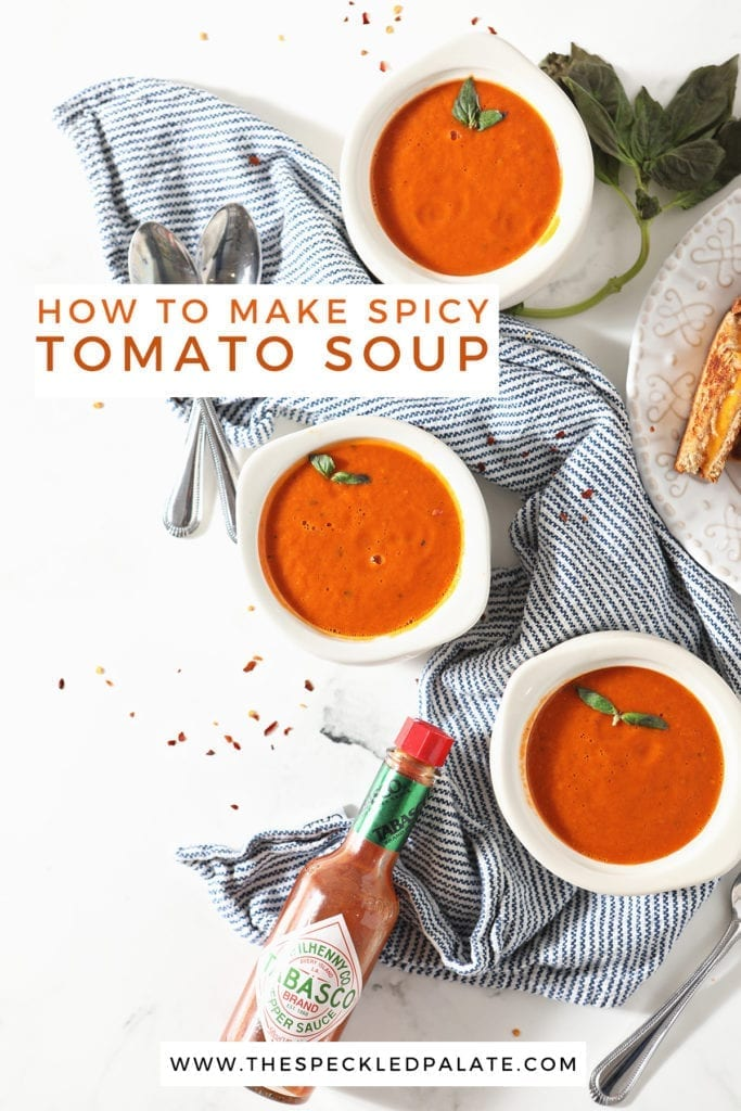 Three bowls of tomato soup sit on a blue striped towel next to a plate of grilled cheese wedges and a bottle of Tabasco with the text 'how to make spicy tomato soup'