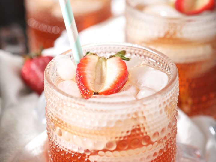Three glasses holding tea with strawberry garnishes