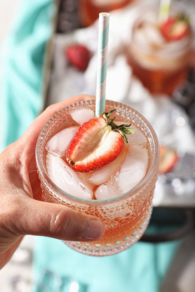 A person holds a glass of homemade strawberry tea garnished with a strawberry half