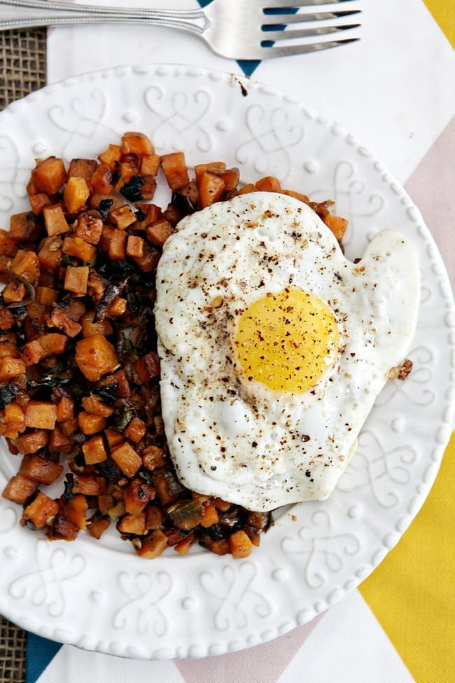 Potato hash and fried egg on white plate